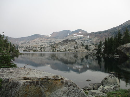 A big clear lake with bare granite mountains with a little snow behind the lake.