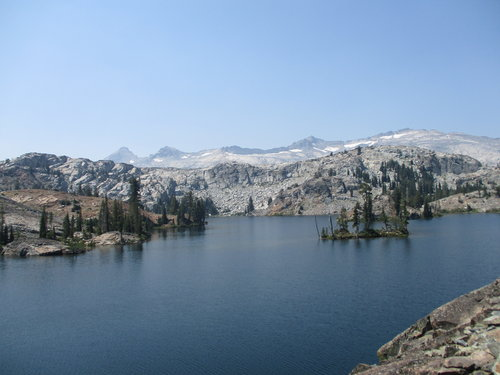 A blue Lake, with granite mountains is the background covered by ribbons of snow.
